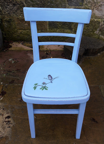 Little painted chair with painted vinyl seat and bird design. The woodwork has been painted in layers of aubergine and bright blue andxa bird on a branch has been added to the old vinyl seat.