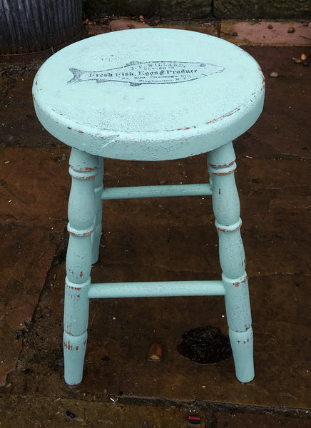 Vintage wooden stool painted in layers of textured paint with fish motif