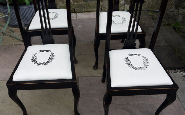 Set of four wooden vintage dining chairs with updated seat pads with a fox and wreath design.