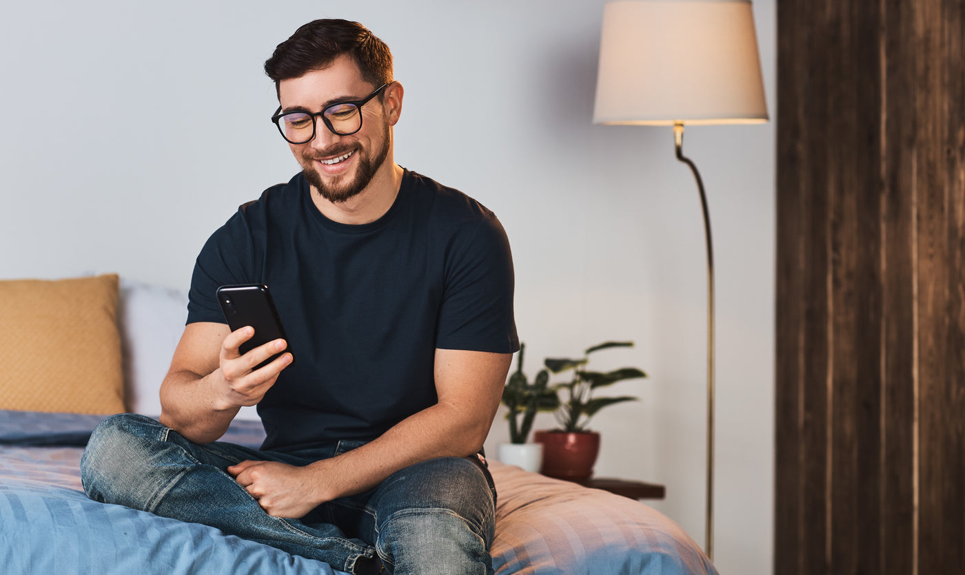 Man sitting on a bed looking at his phone wearing blue light blocking glasses.