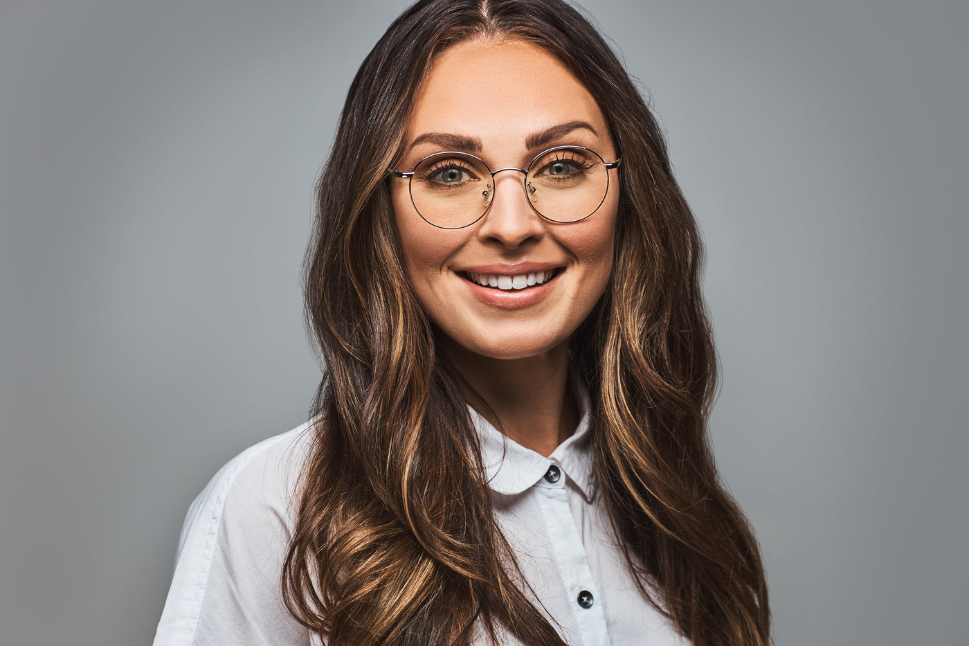 Brown haired woman wearing silver metal frame round shaped blue light blocking glasses.