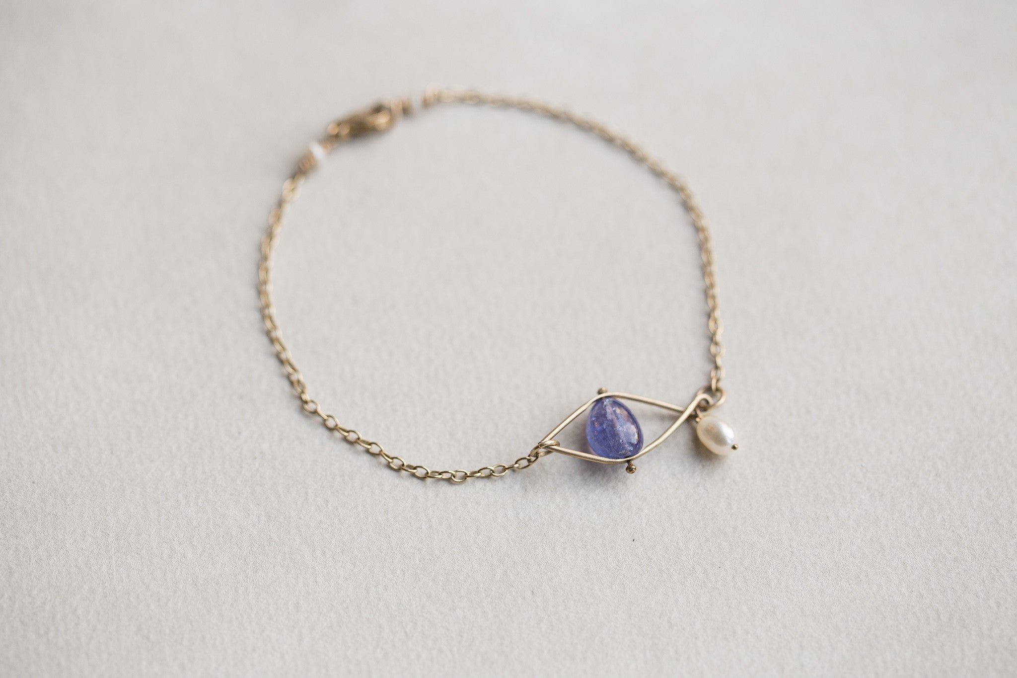 incredibly original eye and tear bracelet, made of 9 carat gold, tanzanite and freshwater pearl