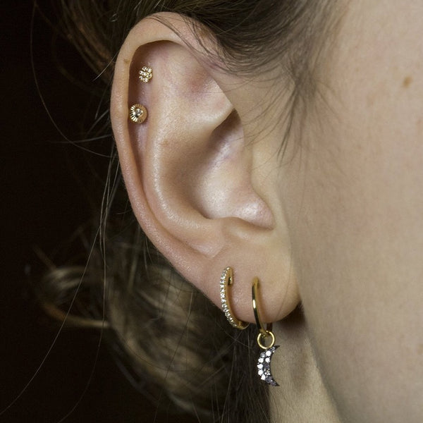 Ella wears 12mm gold plated plain hoop with diamond crescent charm, 12mm white gold diamond hoop, felt's gold etched studs and micro flower stud earrings all available at felt
