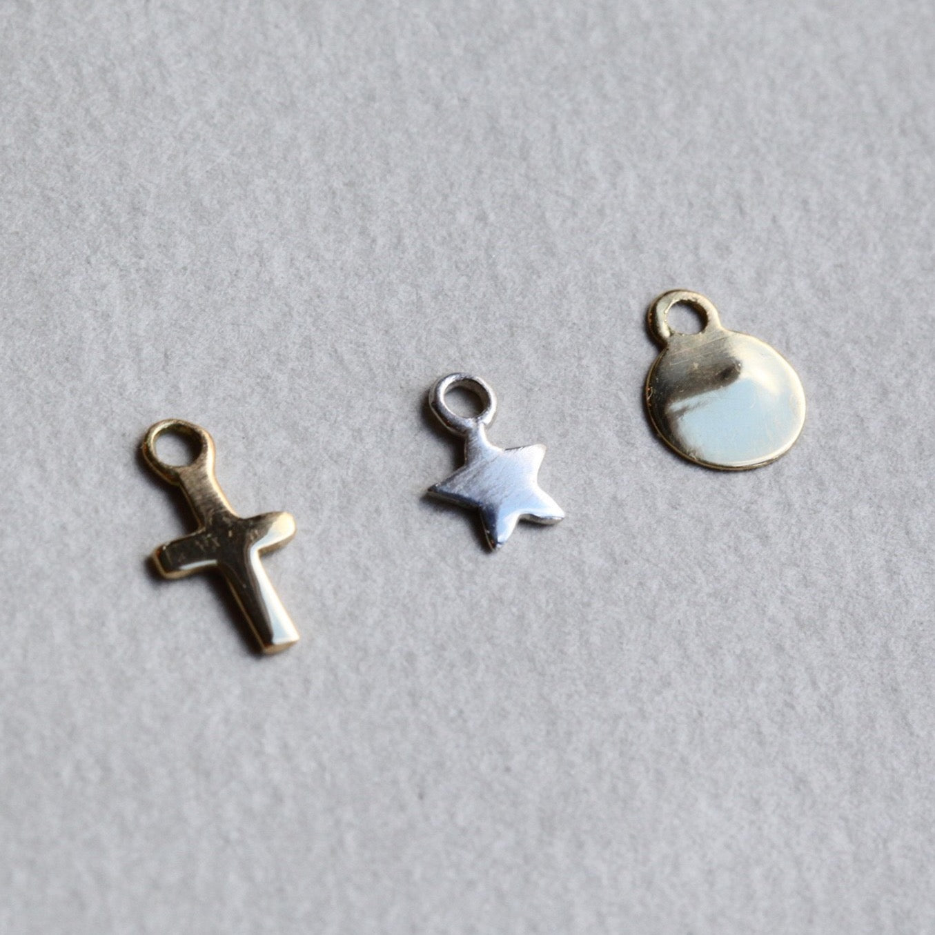 from left: gold plated cross, sterling silver star and 18 carat yellow gold disc