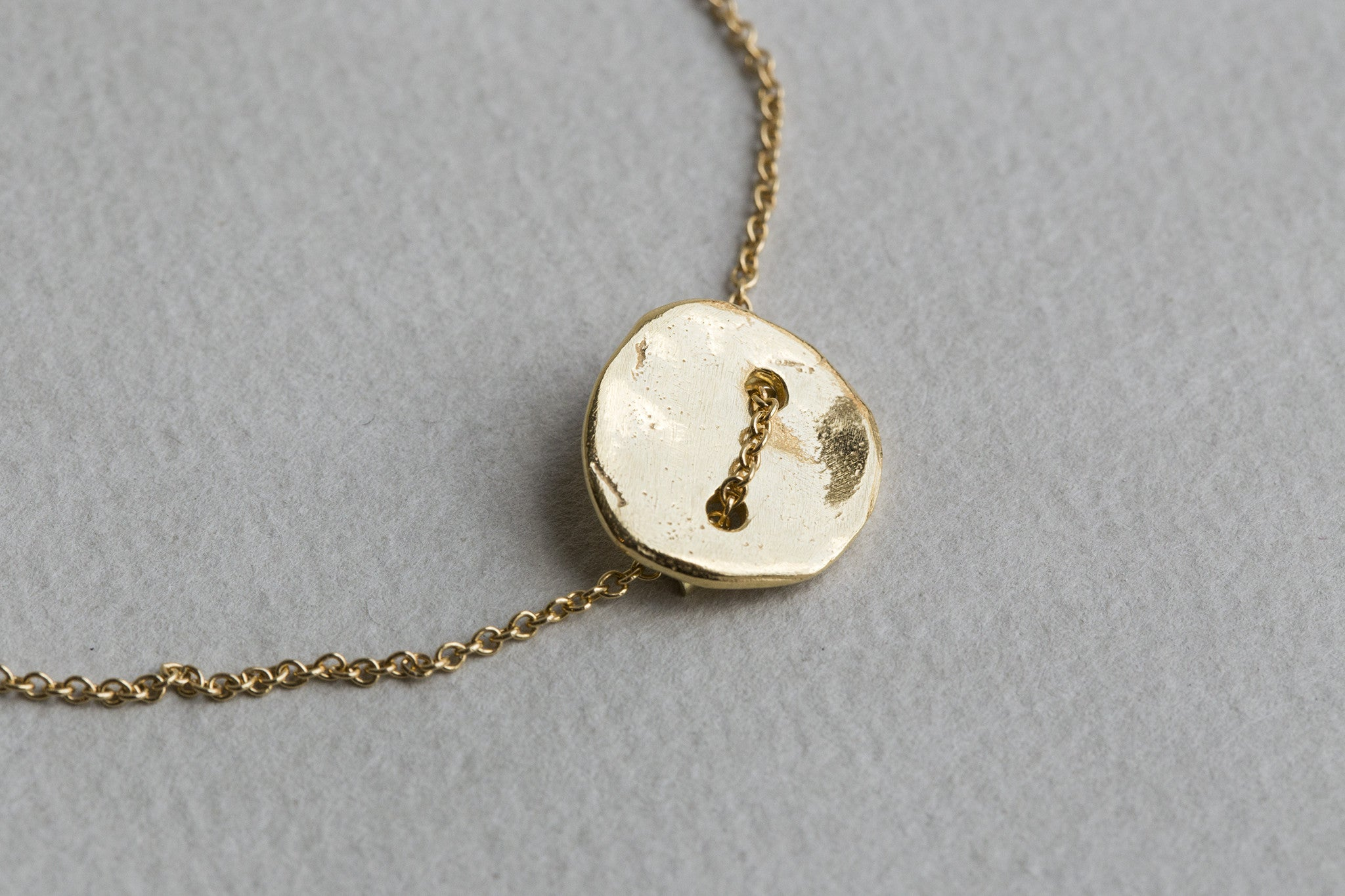 close up of the gold plated hammered button