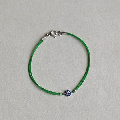 close up of the hot pink and grass green evil eye sterling silver bracelets