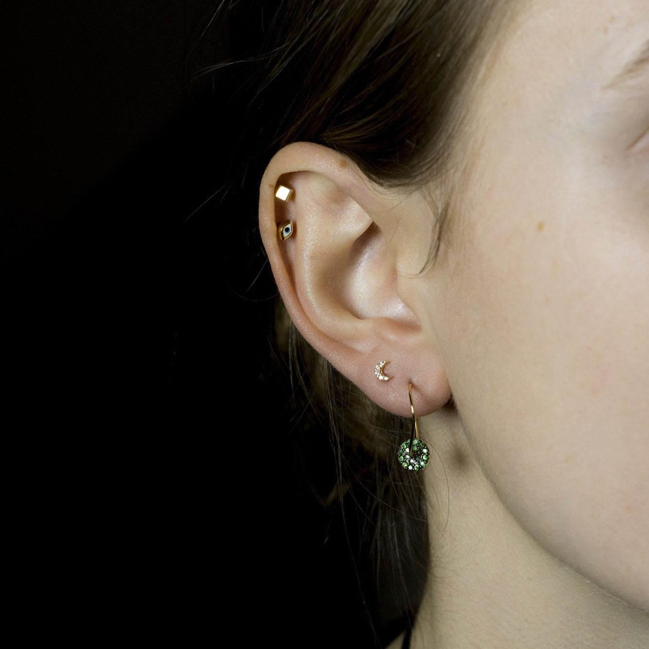 Ella wears wonky hoops with tsavorite discs, Tai crescent stud, felt's gold cube stud and Tai eye earring, all available at feltlondon.com