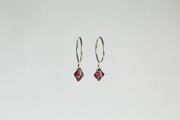 attractively cut garnet hangs from a simple gold hoop