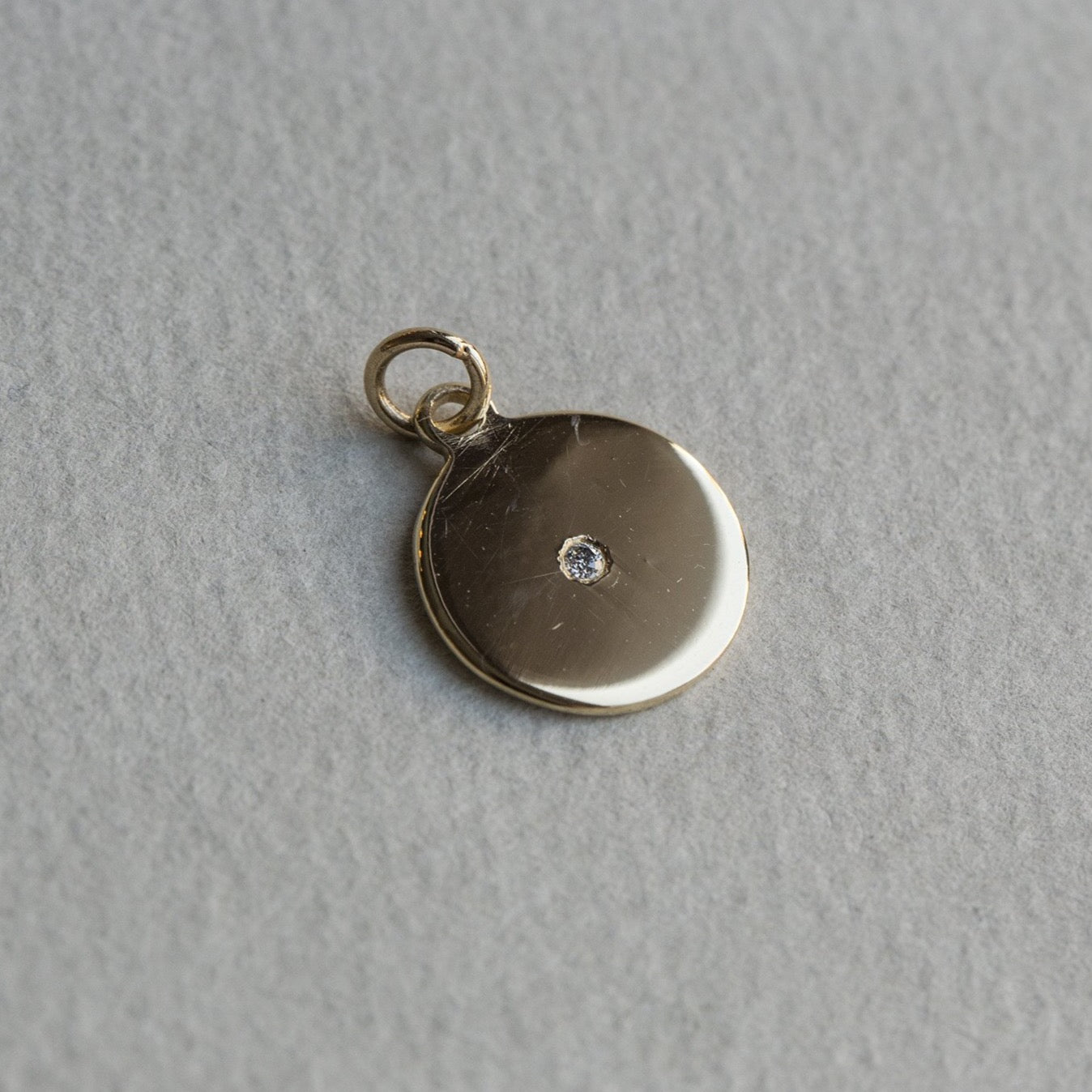 felt's own design - incredibly simple and enchanting polished gold disc with diamond