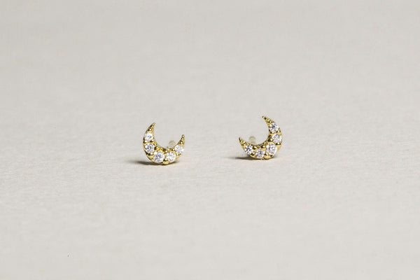 tiny but powerful sparkly crescent stud earrings made of gold plated silver and cubic zirconias