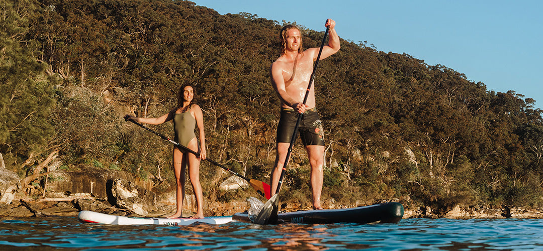 A man and woman having fun on their stand up paddleboards