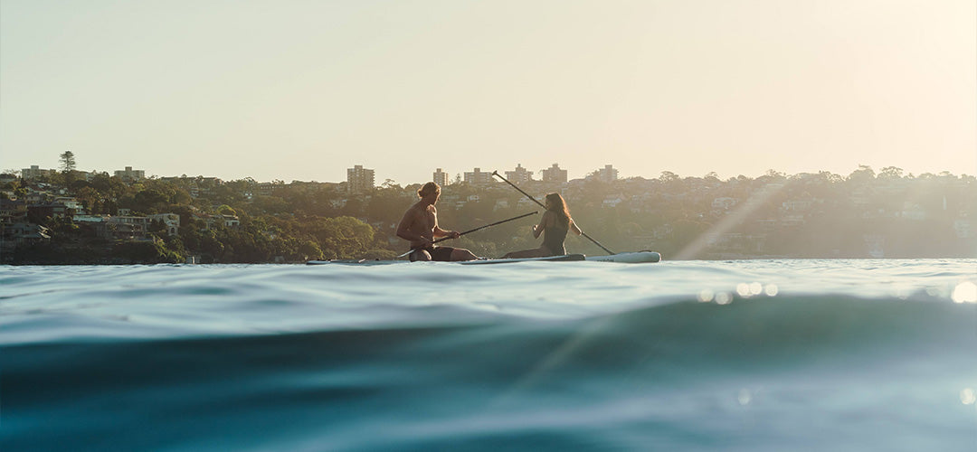 A man and woman sitting on their stand up paddleboards during sunset