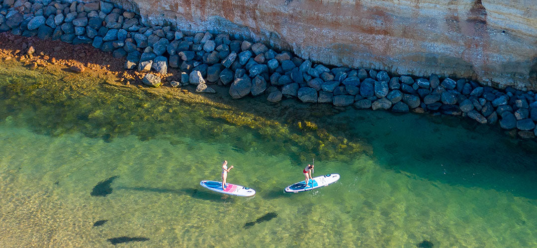 Two girls stand up paddleboarding in Port Noarlunga in South Australia