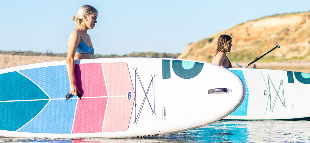 Two girls carrying their inflatable stand up paddleboards