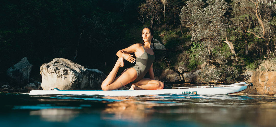 woman doing yoga in paddle board