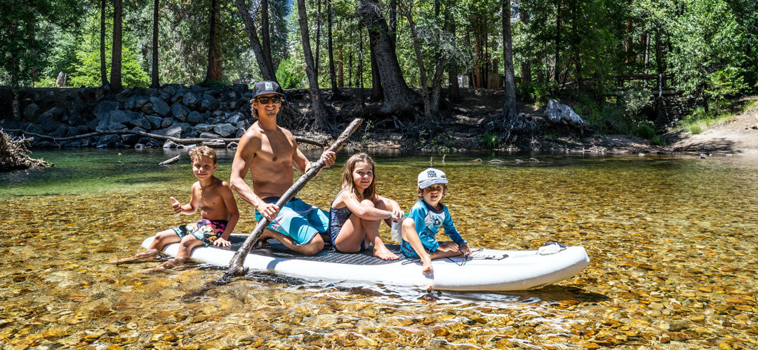 father with his three kids in a paddle board having fun