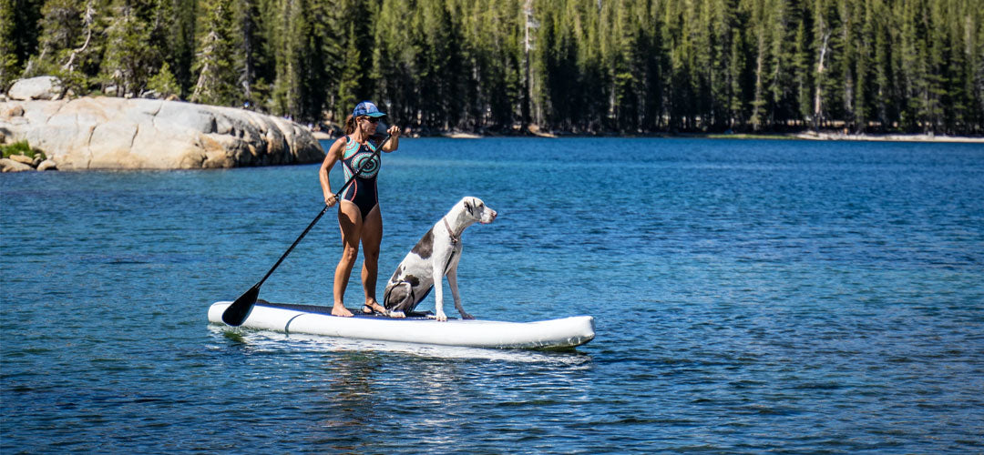 woman with her dog in a paddle board