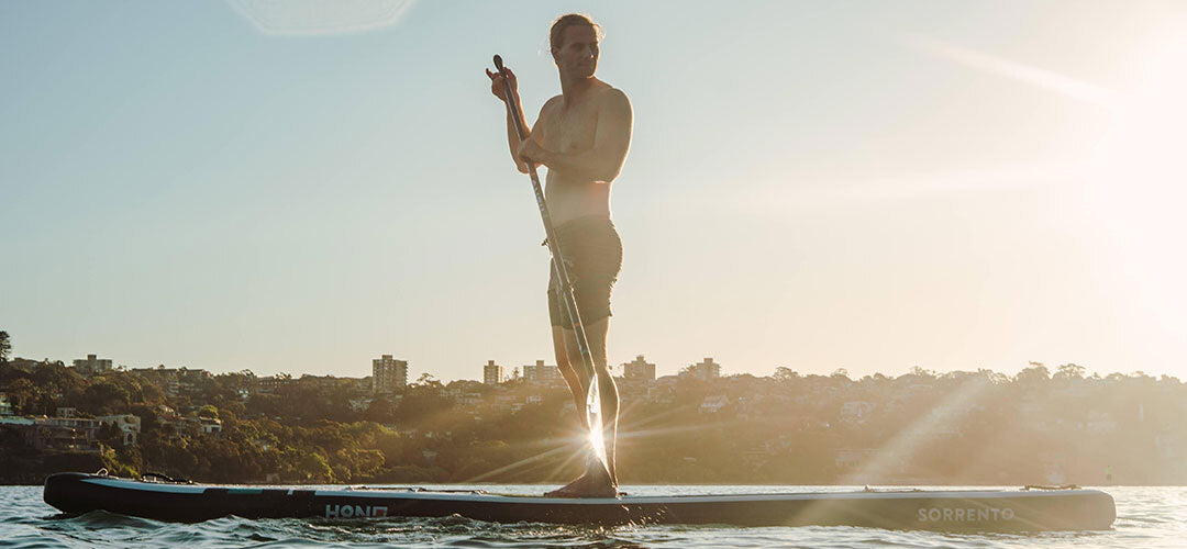 A man on his stand up paddleboard during sunset