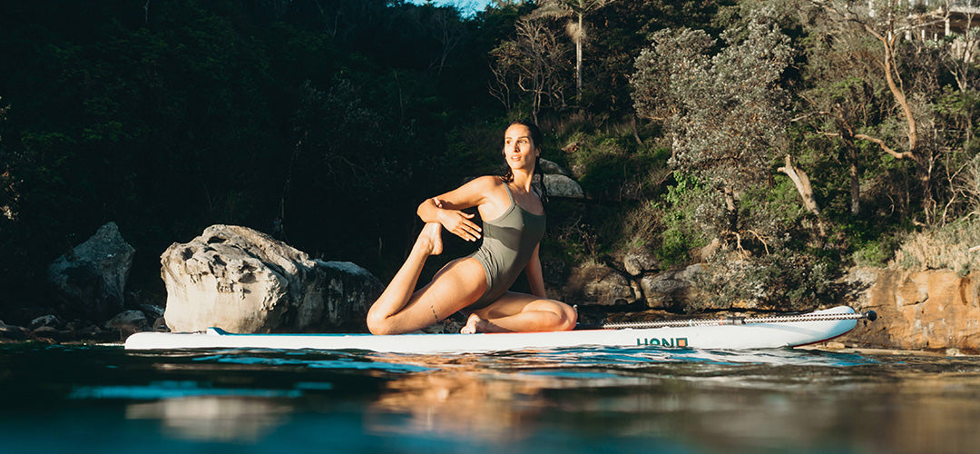 A woman doing yoga on a stand up paddleboard
