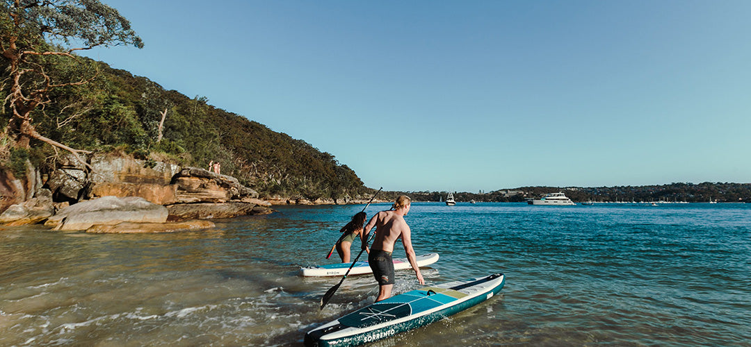 A beautiful beach view with a man and woman hitting the waters to go standup paddleboarding