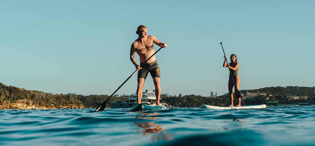 A man stand up paddleboarding during sunset