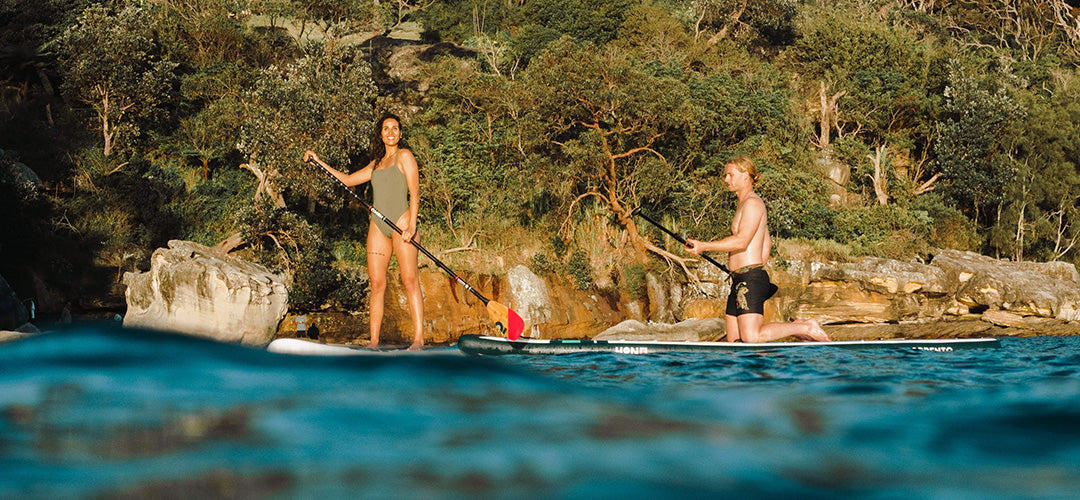A man and woman enjoying their time on their stand up paddleboards
