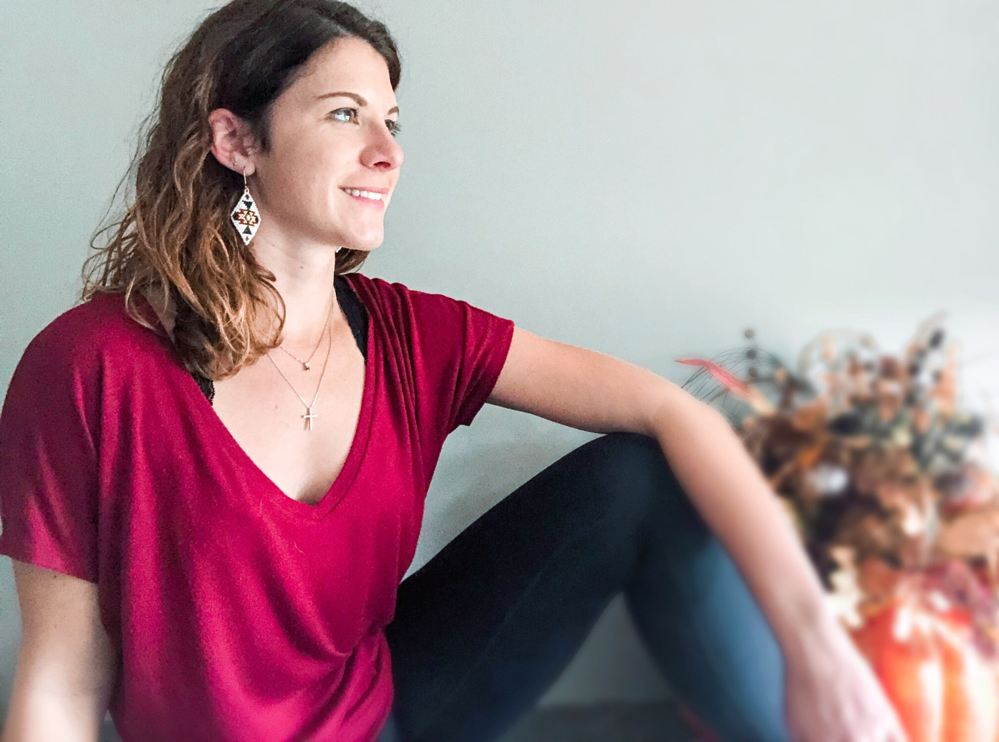 Cait wearing the sweater weather diamond I earrings, red top and black leggings