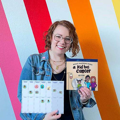 """Founder Sara Olsher holds book, """"What Happens When a Kid Has Cancer"""" and reusable sticker treatment calendar for kids"""