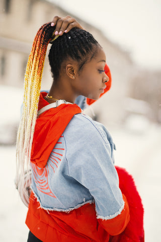 Woman Holding Braids White and Orange Colored