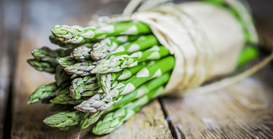 A bundle of asparagus tied in brown paper