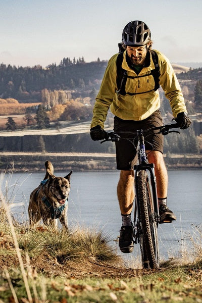 A man and his dog riding through the hills