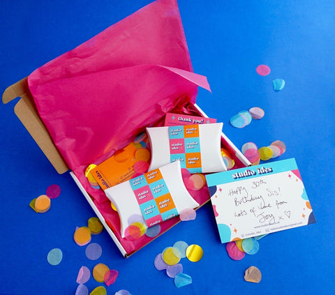 Photograph of typical Studio Ides order, made with brightly coloured paper-based packaging. Includes multicoloured confetti, discount code, handwritten thank you card and independent business card.  Photographed on a bright blue background.