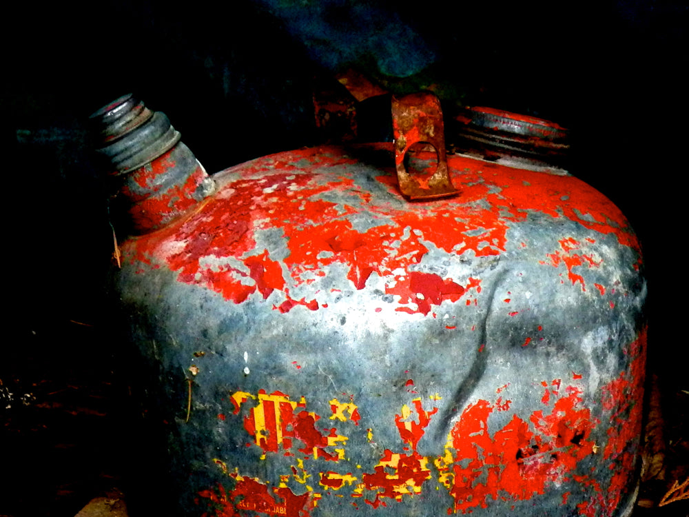 Old gas can. Metal. Patina. Chipped red paint. Texture. Decay.