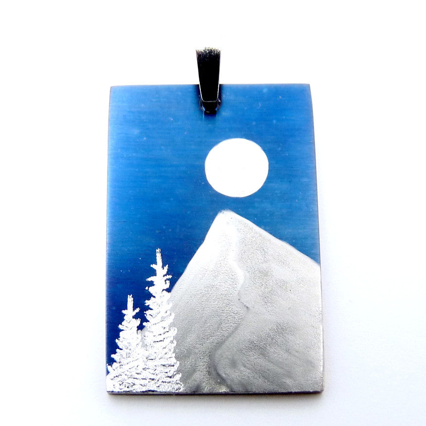 Silver trees, snow capped mountain and full moon on a blue rectangle pendant.