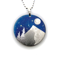 Silver trees, mountain slope and full moon on a blue circle necklace.