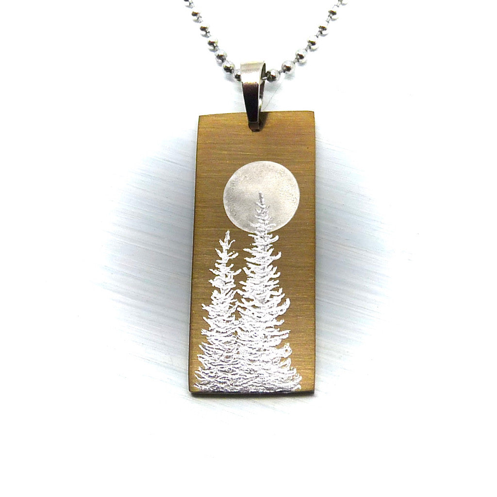 Silver trees and a full moon on a gold vertical bar pendant necklace.