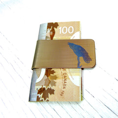 Gold money clip with blue raven on a snag.