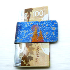 blue speckled money clip with evergreen trees and a full moon.
