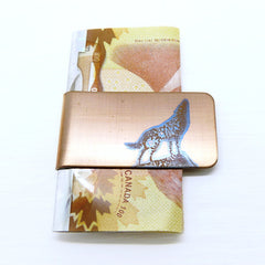 Howling wolf on a gold money clip with cash.