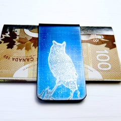 Blue money clip with great horned owl silhouette and cash.