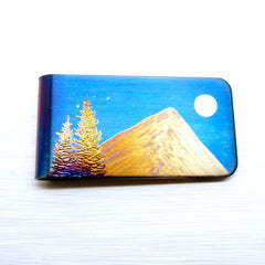 Blue money clip with a gold mountain, evergreen trees and a full moon.