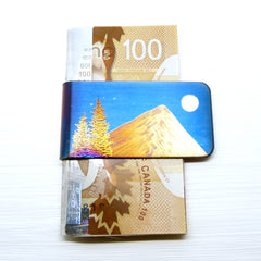 Blue money clip with a gold mountain, evergreen trees and a full moon.  Example with cash.