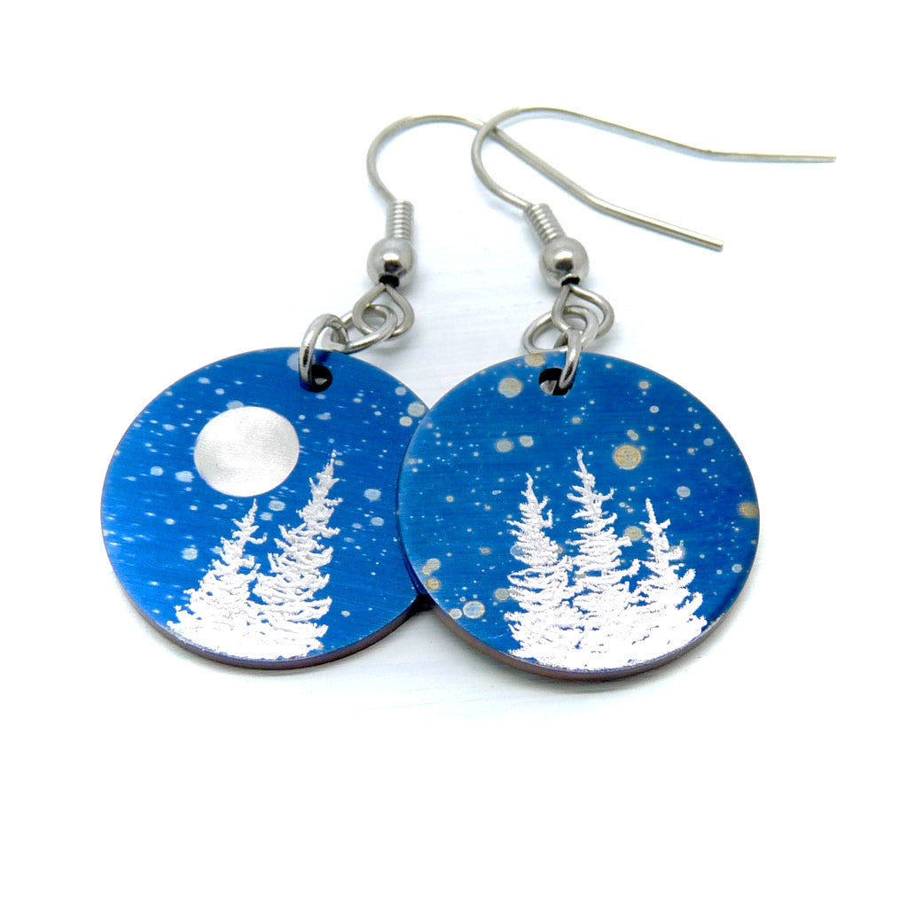 Round earrings in blue with falling snow, silver trees and a full moon.
