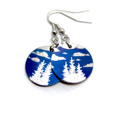 Round earrings, blue sky with clouds and trees.