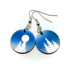 Silver trees and full moon on round blue earrings.