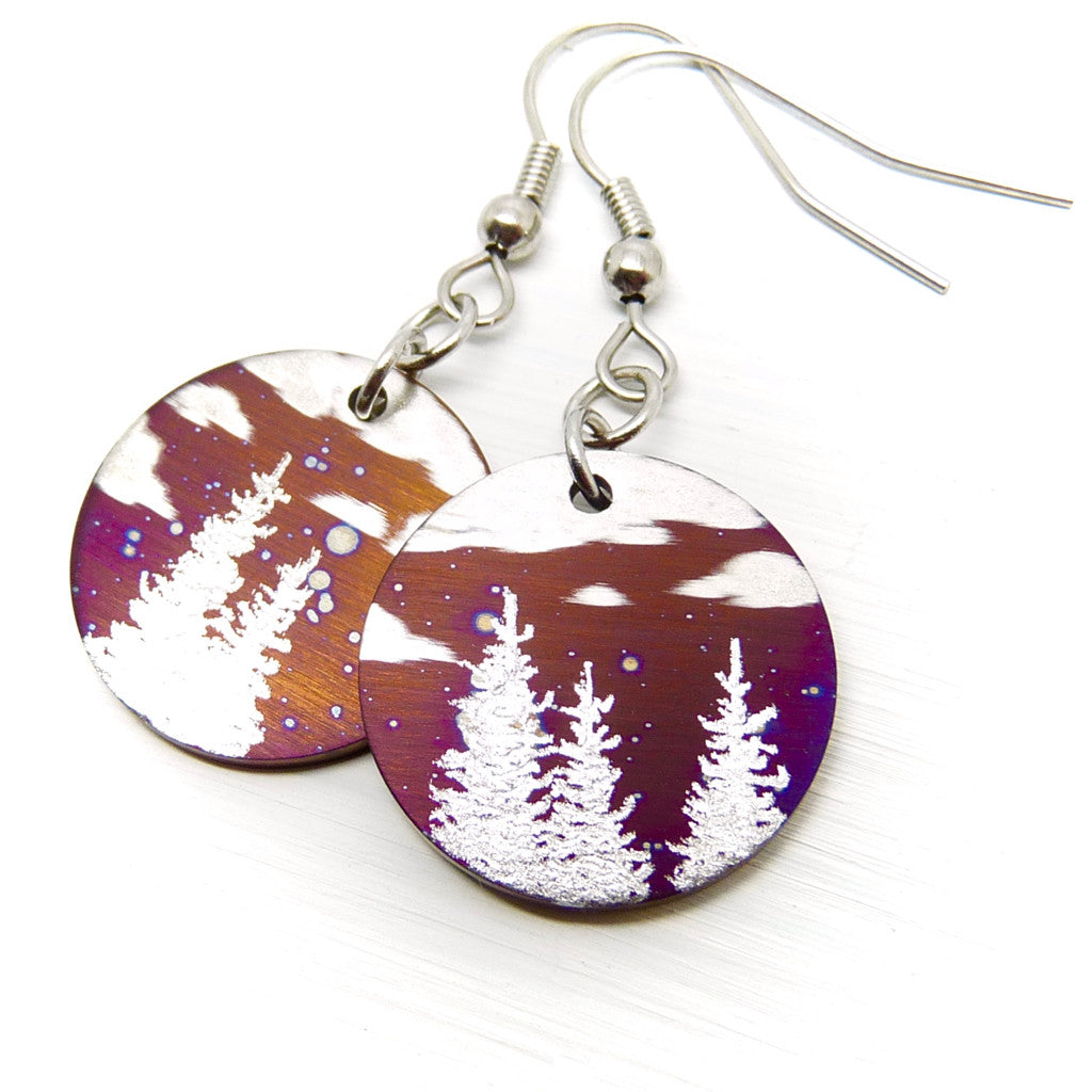 Round earrings with silver trees and clouds.