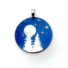 Silver trees and full moon on a blue speckled circle pendant.