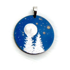Two trees and a full moon on a blue circle necklace.