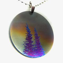 Round necklace with stormy sky and two blue evergreen trees.