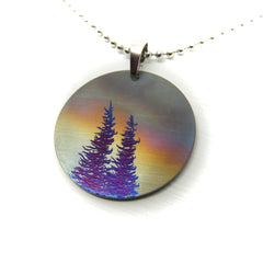Circle necklace with two blue trees and stormy sky.